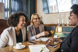 Three women sat around table discussing investment while laughing