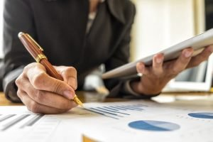 Investment specialist applying pen to printouts of graphs and charts